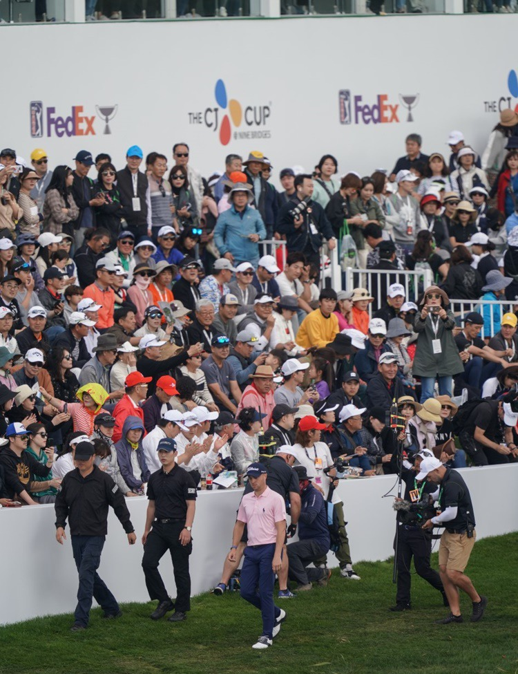 The gallery gathered around the stands near the 18th green