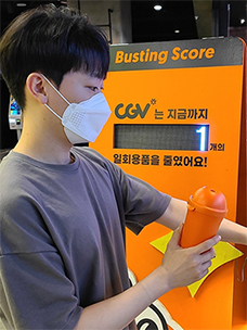 A young man demonstrates how to use a multi-use cup at CGV Deungchon; after receiving your multi-use cup, you press the Busting Score button.